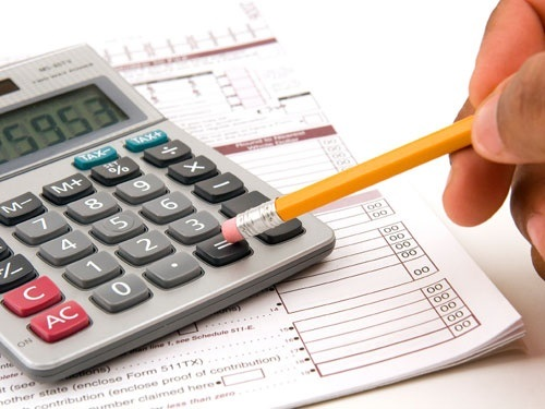 A man doing his taxes using a calculator and pencil on a white background